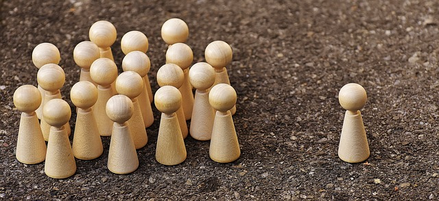 Image Description: a picture displaying a group of pale-coloured wooden pawns all amassed into a group, with the exception of one pawn outside the circle to the left. The larger group of pawns are facing the single pawn as a collective.