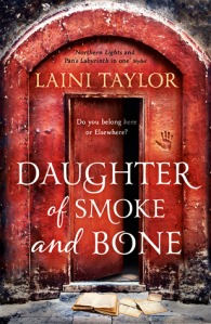 Image Description: book cover of Daughter of Smoke and Bone by Laini Taylor. A red building, red doorway-arch and red door, there is a the imprint of a large hand burned into the right-side of the red-doorway-arch with grey-blue cobblestone/slate-rock on the ground.