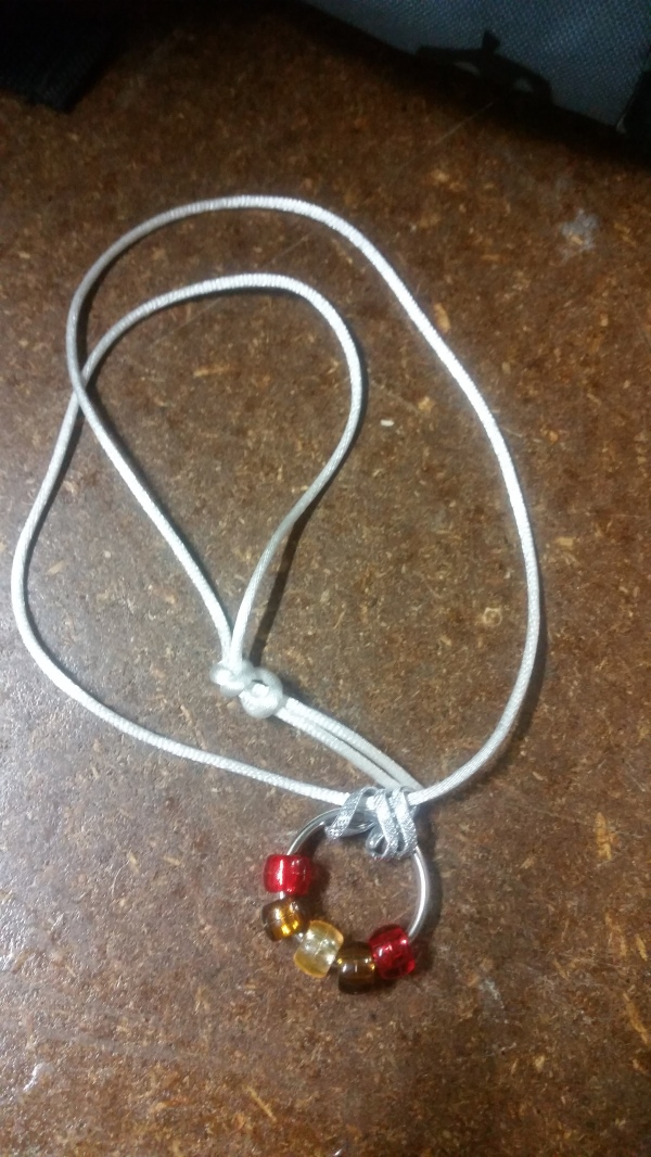 Image Description: a white cord with three chrome-coloured loops, within those three loops is a small metal loop one might use to store keys on, on the loop are five beads with the colour scheme of red-brown-amber-brown-red