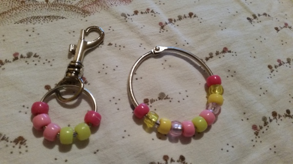 Image Description: There are two items in this picture. Left to right, Item One is a chrome metal object that functions as a metal clip, sometimes used for keys or attaching to bags. It has a metal loop one might use to store keys on. It has six beads on the metal loop, the colour scheme is dark pink-light pink-light pink-yellow-yellow-dark pink. Item Two is a small metal loop, one might confuse it for a child's bracelet, it has eleven beads, the colours are a variant mixture of pink and yellow but the beads are also a mixture of solid plastic and transparent plastic