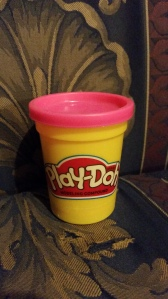 Image Description: a small yellow container of play-do with a pink lid.