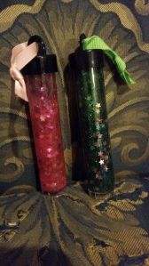 Image Description: Left to right, a plastic tube filled with liquid pink glitter and silver stars with a pink ribbon on top, as well as a plastic tube filled with liquid green glitter and silver stars with a green ribbon on top.