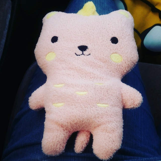 Image Description: weighted plushie that possibly looks like a bear, a dog, a bear-dog, or a cat. Light pink in colour with a yellow crown on her head, with yellow blush circles on both sides of her cheeks and little yellow circles on her stomach and a little tail