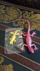 Image Description: Left to right, a small yellow rubber lizard which is also kind of sticky and a larger pink rubber lizard