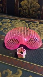 Image Description: top to bottom, a bright-pink cylindrical slinky in an arch shape with a smaller star-shaped pink and yellow slinky