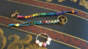 Image Description: top to bottom, a long dark-blue string key-chain intertwined with a rainbow spectrum of beads, a lighter-blue string with a metallic rainbow spectrum of beads and a small chrome circle with pink-white-purple-white-pink beads