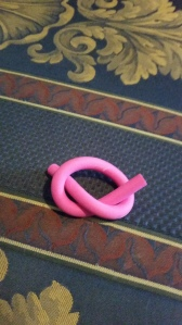 Image Description: a bright-pink eraser in the shape of a string currently folded into a vague pretzel shape