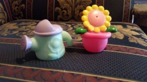 Image Description: two small bath toys, left to right, a purple and robin's egg blue water-can and a a yellow and pink flower with a bright-pink pot. you can use them to blow at people or yourself.