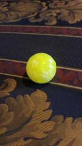 Image Description: a bright yellow bouncy ball
