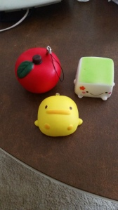 Image Description: left to right, a squishable red apple, in the center a small squishable duck, on the right-hand side a small square slice of tofu with green on the top (I should also like to add that the tofu square is also squishable)