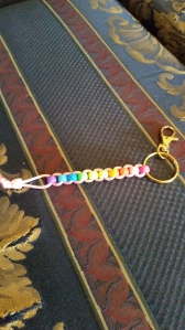 Image Description: a lanyard made of a rainbow scale of beads and pink cord