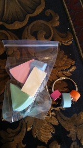 Image Description: a collection of squishy foam objects in a bag and a chrome metal wrong with three foam objected embedded on it