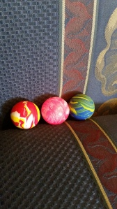 Image Description: three bouncy balls, left to right, one that's red and yellow, one that's pink and white, one that's blue and green swirls.