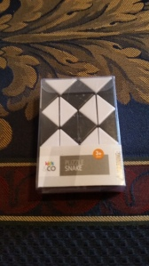 Image Description: a black and white checked snake puzzle in a plastic box