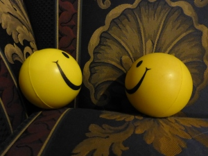 Image Description: Two smiley-face stress-ball facing off against each other