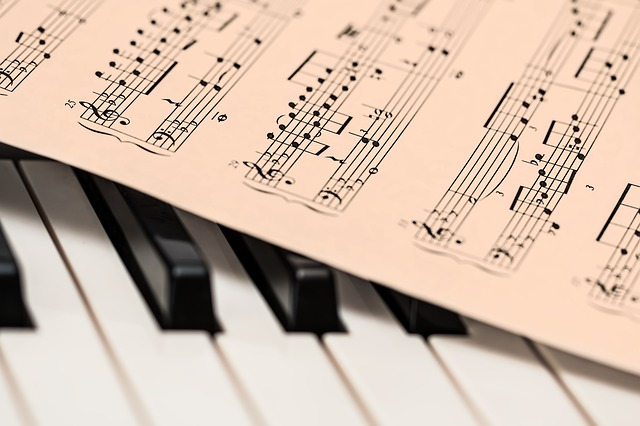 Image Description: The keyboard of a piano with a single page of sheet music on top of it