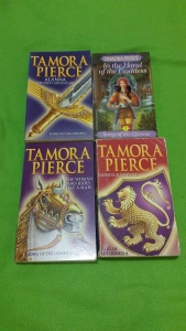Image Description: a collection of four books on a green blanket, the books are The Song of the Lioness series by Tamora Pierce