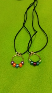 Image Description: two necklaces with black cord, four chrome-coloured small loops and a key ring with beads on them, from left to right, the first necklace has purple-orange-blue-orange-purple coloured beads. The second necklace has light blue-dark blue-purple-dark blue-light blue coloured beads.