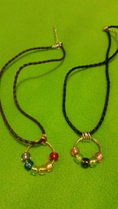 Image Description: from left to right, there are two necklaces with shorter cords that look like two cords intertwined together. The first one is a short brown cord with two brown cords intertwined together, with four gold-coloured small loops and a gold key ring with light blue-dark blue, green, yellow, amber and red coloured beads. The second one is a short black cord with two black cords intertwined together, with four silver-coloured small loops and pink-green-black-green-pink coloured beads