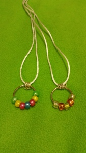 Image Description: two necklaces with white cord, four chrome-coloured small loops and a key ring with beads on them, from left to right, the first necklace has green-yellow-pink-blue-pink-yellow-green coloured beads. The second necklace has white-orange-yellow-orange-white coloured beads