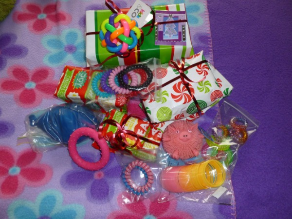 a collection of gifts wrapped in Christmas themed wrapping paper (I'll go into detail within the post). What can be seen is a large Kids &Co. multi-coloured large bouncy ball, a pink pig critter puff, a pink and yellow slinky, a large blue balloon filled with flour, a pink circle with raised dots on it and multiple zip-lock bags with telephone cord hair-ties inside them.