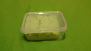Image Description: a small clear Tupperware container filled with green fake kinetic sand.