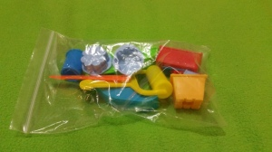 Image Description: a clear zip-lock bag with a colourful collection of fake kinetic sand moulds and tools.
