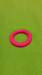 Image Description: a pink rubber-circle with raised dots on it.