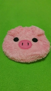 Image Description: A small furry purse that resembles a pink pig