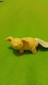 Image Description: Tiny figurine of a pig that is pink and yellow