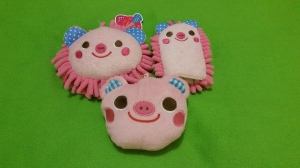Image Description: Two pink sponges in the shape and form of pigs with pink fronds exiting them with a small coin purse in the shape of a pig just beneath them.