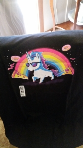 Image Description: a black t-shirt with a unicorn waring shades with a rainbow in the background, with doughnuts and slices of pizza floating in the background