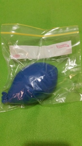 Image Description: a large dark-blue balloon filled with flour sealed in a clear-plastic zip-lock bag.