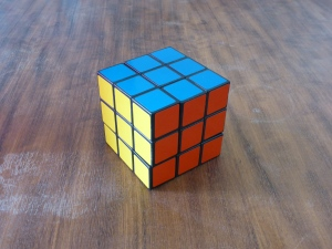 Image Description: A perfectly formed Rubric cube with the red, blue and yellow sides showing