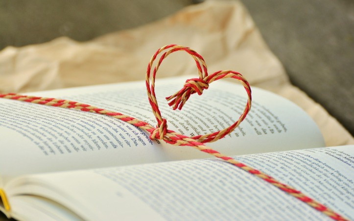 Image Description: a picture of an open book with red and yellow string in the shape of a heart