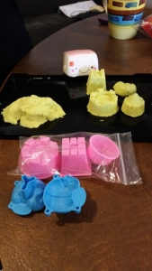 Image Description: A black lipped-tray with yellow fake kinetic sand in a pile at one end and moulded piles at the other end of the tray. In front of the tray is a zip-lock bag filled with pink sand castle moulds and a blue caterpillar mould. Behind the tray, there is a tofu squishy with on top pink lurking behind the kinetic sand.