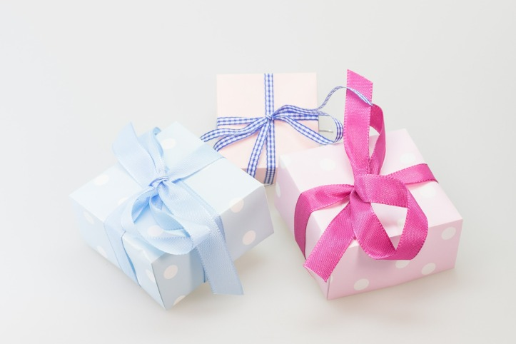 Image Description: from left to right, a robin's egg blue gift box wrapped with robin's egg blue ribbon, a pink gift box with navy blue ribbon tied around it, a light-pink polka-dotted-box with dark-pink ribbon tied in a bow on top