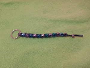 Image Description: plastic bead lanyard in varying shades of green and purple with a silver bead at the end