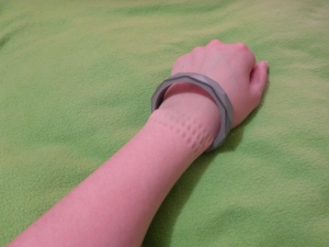 Image Description: silver chewable bangle bracelet on a white arm, resting loosely around the wrist