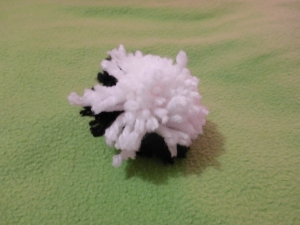 Image Description: black and white yarn poof ball