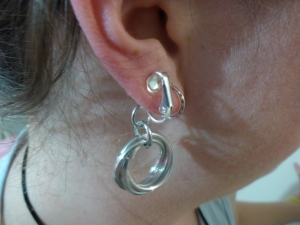 Image Description: Clip on earrings with silver color interlocking rings clipped on my ear (to show scale)