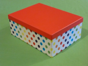 Image Description: a medium sized white box with a rainbow-spectrum of polka-dots decorating the outside with a bright-red lid on top