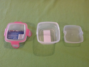Image Description: a pink Crofton Snack Container 400 mL that has been separated into it's three parts, from left to right are lid/top, bottom of the container and the opaque in-between layer