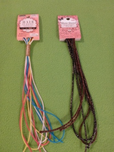 Image Description: there are two items in the photo, from left to right, the first item is a packet of Hair Elastics in pink, yellow, white and blue. The second item is a packet of hair bands in brown hair-bands with silver-sparkles mixed in and black hair-bands with silver-sparkles mixed in.