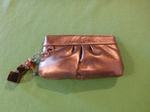 Image Description: A small bronze-coloured clutch-purse with various brown key-ring accessories attached to it.