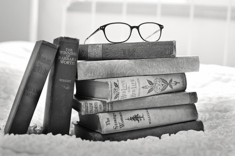 Image Description: a black and white photo of a pile of books with a pair of glasses on top