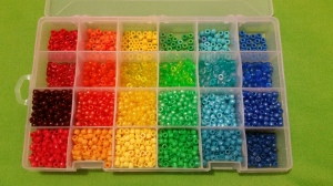 Image Description: a Jarvis Walker worm-proof lure-box with adjustable compartments. There's four compartments down and six compartments across. The six across compartments are sorted by colour (red, orange, yellow, green, light blue and dark blue). The four compartments down are sorted by type of bead (acrylic, transparent, pearlized, and matte hour-glass shaped beads). In this photo, the are two empty compartments mentioned in the previous photo have been filled with cranberry-red (it's more of a dark red really) pearlized beads and light blue pearlized beads