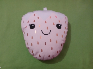 Image Description: A cushion in the shape of a pale-pink strawberry with a cute smiley face and gold-coloured seeds