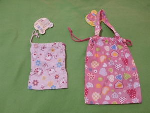 Image Description: from left to right, a small pale-pink bag with flowers and bunnies printed on it. Next to the pale-pink bag is a dark-pink with multicoloured hearts printed on it