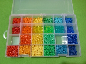 Image Description: a Jarvis Walker worm-proof lure-box with adjustable compartments. There's four compartments down and six compartments across. The six across compartments are sorted by colour (red, orange, yellow, green, light blue and dark blue). The four compartments down are sorted by type of bead (acrylic, transparent, pearlized, and matte hour-glass shaped beads). In the photo, there are two compartments empty: red pearlized beads and light blue pearlized beads.